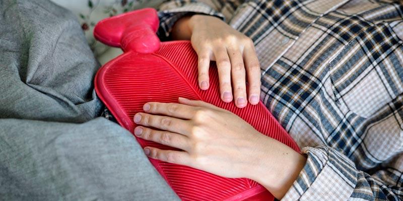 Termofor czerwony grzeje chorego w łóżku